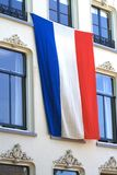 Dutch flag on building. Huge dutch national flag hanging from an historical building royalty free stock photos