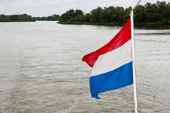 Dutch flag fluttering above water. Dutch flag of a sightseeing boat  fluttering above turbulent water in the Dutch National Park De Biesbosch Stock Image