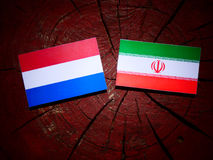 Dutch flag with Iranian flag on a tree stump isolated Royalty Free Stock Image