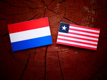 Dutch flag with Liberian flag on a tree stump isolated. Dutch flag with Liberian flag on a tree stump Stock Photography
