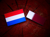 Dutch flag with Qatari flag on a tree stump isolated. Dutch flag with Qatari flag on a tree stump Royalty Free Stock Photo