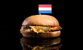 Dutch flag on top of hamburger isolated on black Royalty Free Stock Images