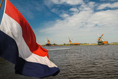 Dutch flag and windmills. A dutch flag with in the background three windmills. With a blue sky and some clouds Royalty Free Stock Photo