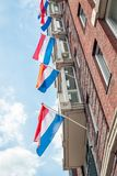 Dutch flags fluttering above each other. Dutch flags,  attached to white flagpoles on a brick facade, fluttering above each other. The photo was taken on a sunny Royalty Free Stock Images
