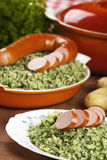 Dutch food: kale with smoked sausage or 'Boerenkool met worst'. A rustic table with a plate with 'Boerenkool met worst' or kale with smoked sausage, a Stock Image