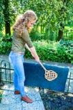 Dutch girl beating door mat with carpet beater. Young caucasian woman beating door mat with carpet beater outside Stock Photo