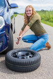 Dutch girl changing car wheel on country road Stock Photography