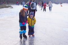 Dutch girl little brother ice skate lessons frozen lake, Netherlands Stock Photo