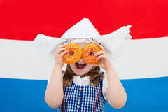 Dutch girl with orange donuts and Netherlands flag. Little Dutch girl wearing traditional national costume, dress and hat holding orange donuts at flag of the Stock Image