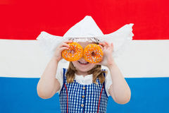 Dutch girl with orange donuts and Netherlands flag. Little Dutch girl wearing traditional national costume, dress and hat holding orange donuts at flag of the Stock Photos