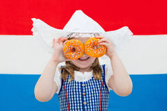Dutch girl with orange donuts and Netherlands flag Royalty Free Stock Images