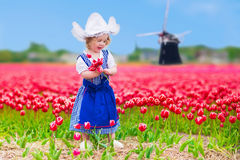 Dutch girl in tulip field in Holland. Adorable curly toddler girl wearing Dutch traditional national costume dress and hat playing in a field of blooming tulips Royalty Free Stock Photos
