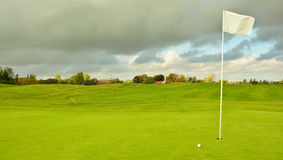 Dutch golf course. Dutch polder golf course with dark clouds. Golf ball near the holl with white flag Royalty Free Stock Photo