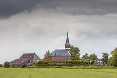 Dutch Hamlet of Warstiens. With church and several farm barns in dairy landscape near city of Leeuwarden, Friesland, the Netherlands royalty free stock images