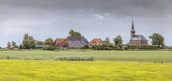 Dutch Hamlet of Warstiens. With church and several farm barns in dairy landscape near city of Leeuwarden, Friesland, the Netherlands stock image
