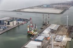 Dutch harbor Eemshaven with wind turbines and offshore construction platforms. Dutch harbor Eemshaven with wind turbines and off shore construction platforms stock photography