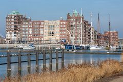 Dutch Harbor of Lelystad with sailing yachts and apartment building. Lelystad, The Netherlands - February 23, 2019: Harbor with sailing yachts and modern royalty free stock photo