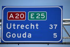 Dutch highway sign on motorway A20 E25 the kilometer distance to the city of Gouda and Utrecht.  royalty free stock image