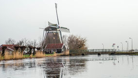 Dutch historic water mill on gray winter morning. Ancient structure lined with bridge over icy canal and pollarded willows Royalty Free Stock Image