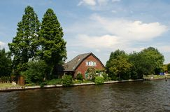 Dutch house, garden, canal and trees Royalty Free Stock Photography
