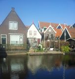 Dutch houses with reflections in canal. Dutch houses in village of Volendam against blue sky with reflections in rippling canal in North Holland, the Netherlands Stock Photos