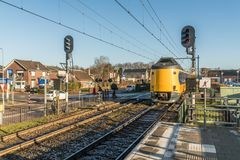 Dutch Intercity train with germand wagons passing the village during wintertime. Twelllo, the Netherlands, December 17th 2017: Dutch Intercity train with germand Royalty Free Stock Photo