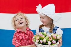 Dutch kids with tulip flowers and Netherlands flag Royalty Free Stock Images