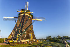 Dutch land keeper house and windmill. Garden of the Dutch land keeper at the early morning, at the sunny blue hours and before starting its duties against the stock images