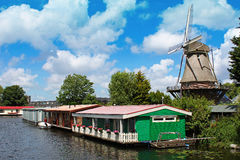 Dutch landscape. Amsterdam suburbs - Dutch countryside landscape with a windmill and houseboats royalty free stock photo