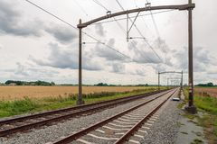 Rusty train tracks with overhead lines in the Netherlands. Dutch landscape with, diagonal in the image, rusty and seemingly endless long train tracks with royalty free stock image