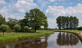 Dutch landscape with a view over the river Mark. Meadows, reflected trees and a blue sky with wonderful clouds Royalty Free Stock Photo