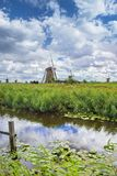 Dutch landscape with windmills in a field and dramatic clouds. royalty free stock image