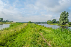 Dutch Landscapes - Baarn - Utrecht. Walking path over a dike through typical Dutch landscape with a cloudy blue sky Stock Photography