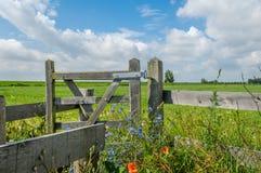 Dutch Landscapes - Baarn - Utrecht. Wooden fence in Dutch landscape against cloudy blue sky Stock Image