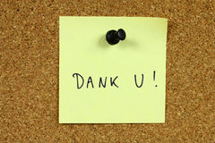 Dutch language. Yellow sticky note pinned to an office notice board. Dank u - thank you in Dutch royalty free stock image
