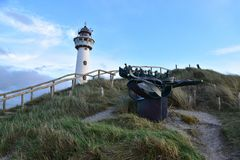 Dutch lighthouse and boat statue in Egmon aan Zee. Dutch lighthouse and people in a boat statue, in Egomnd aan Zee, coastal village in The Netherlands Royalty Free Stock Photo