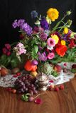 Dutch Masters Inspired Still Life of Bright Flowers and Fruit. Modern take on a classic style. Lush and vibrant colors; abundant, spilling fruits. Celebration Stock Photography