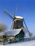 A Dutch mill in a winter landscape Stock Images
