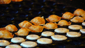 Dutch mini pancakes called poffertjes. Baking small dutch traditional poffertjes in Holland Royalty Free Stock Photography
