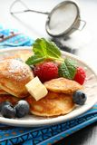 Dutch mini pancakes called poffertjes with berries Stock Image