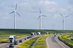 Dutch motorway near Lelystad with wind turbines and blooming rapeseed. Dutch motorway A6 near Lelystad with wind turbines and blooming rapeseed stock photography