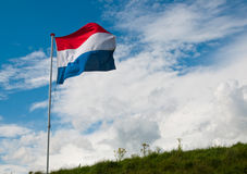 Dutch national flag waving in the strong wind. Top of a dike in the Netherlands with the Dutch national flag waving in the wind Royalty Free Stock Photo