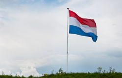 Dutch national flag waving in the wind. Top of a dike in the Netherlands with the Dutch national flag waving in the wind Stock Photography