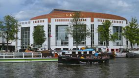 Dutch National Opera, Amsterdam, Netherlands. Excursion Boats at De Nationale Opera, Dutch National Opera, opera, Amstel Canal, Amsterdam, Holland, Netherlands stock footage