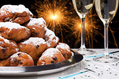 Dutch New Year's Eve with oliebollen, a traditional pastry. 'Oliebollen', traditional Dutch pastry for New Year's Eve and two glasses of champagne Royalty Free Stock Photo