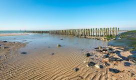 Dutch North Sea coast at low tide. Overview of the Dutch North Sea coast with a small part of a long asphalt-covered seawall. In the sea is a traditional Stock Photo