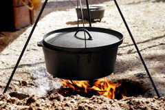 Dutch Oven Cooking Over Open Flame. A traditional Dutch Oven, suspended on a tri-pod over an open flame campfire, cooking a meal royalty free stock images