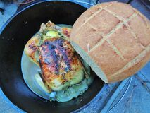 Dutch Oven Cooking, Rosemary Chicken e pão integral duro do ferro do artesão fotografia de stock royalty free