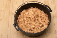 Dutch oven filled with homemade Apple Crumble pie on a wooden kitchen floor stock images