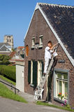 Dutch painter stands on ladder painting eaves. Netherlands, South Holland province, city, small town Goedereede, island and municipality Goeree-Overflakkee: in Royalty Free Stock Photo